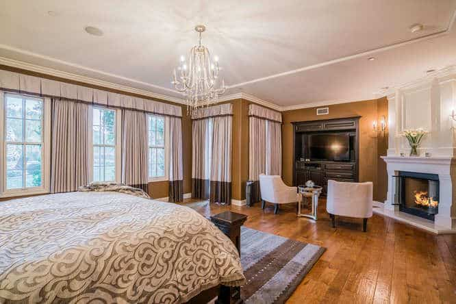 Large master bedroom with brown walls and hardwood floors. It offers a large cozy bed and a fireplace, along with a living space on the side featuring a TV.