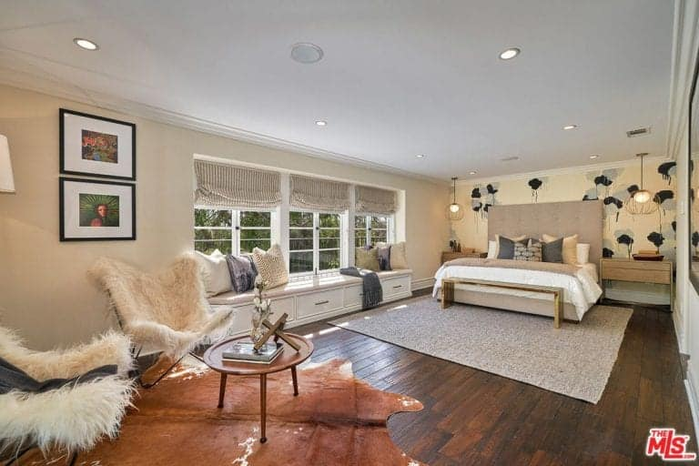 Spacious master bedroom with beige walls and hardwood floors. The room has a large bed set with built-in bedside tables on both sides lighted by pendant lights above it.