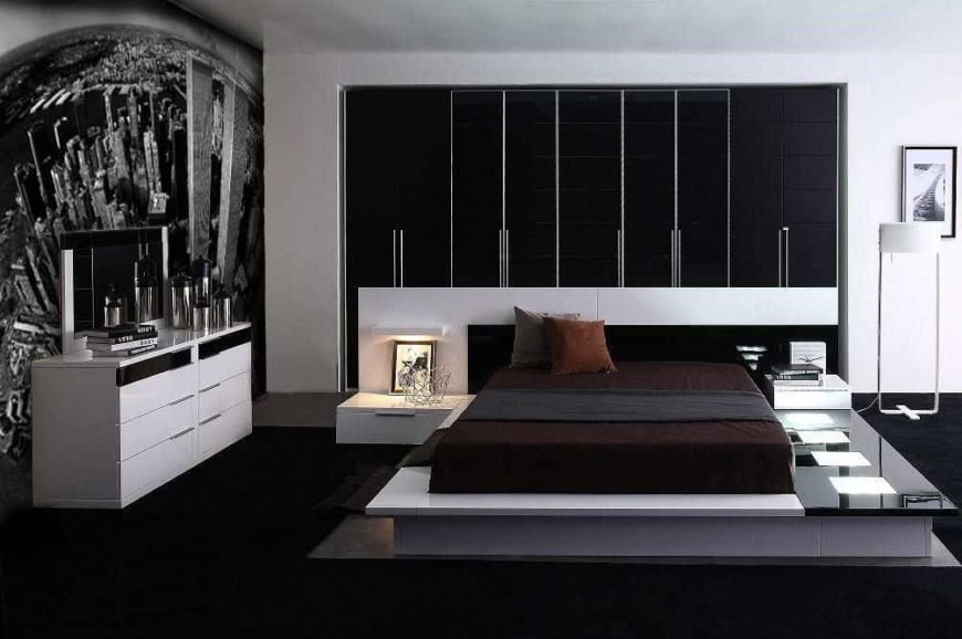 Contemporary master bedroom with a black and white color scheme. It has a stylish bed setup with built-in bedside tables. The wall features an eye-catching design.