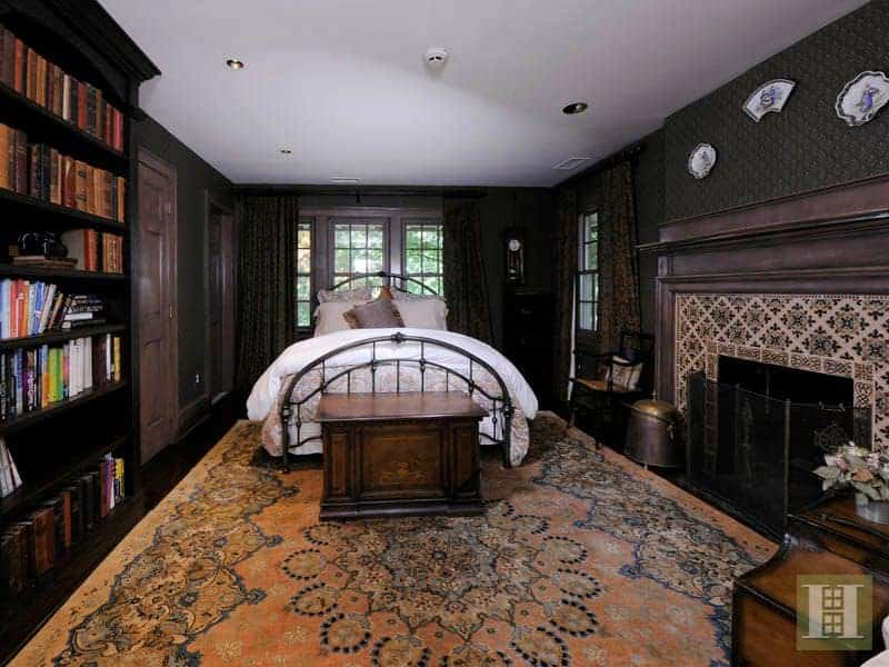A master bedroom with elegant black walls. It features a large bookshelf along with a large decorated fireplace. The dark hardwood flooring is topped by a large stylish area rug.