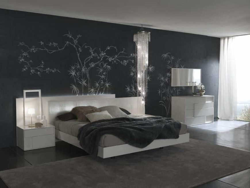 Contemporary master bedroom boasting a decorated black wall along with a white bed set with white bedside tables. The dark tiles flooring is topped by a gray area rug.