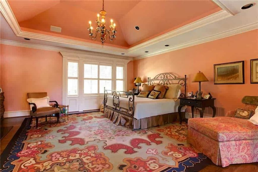 Large master bedroom featuring orange walls and ceiling, along with hardwood flooring topped by a large area rug. The room offers a gorgeous bed setup lighted by a pair of table lamps and a small gorgeous chandelier.