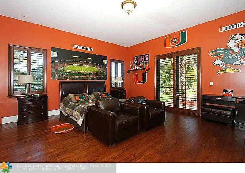 This master bedroom features orange walls and hardwood floors. The room has a classy bed set together with dark brown leather seats.