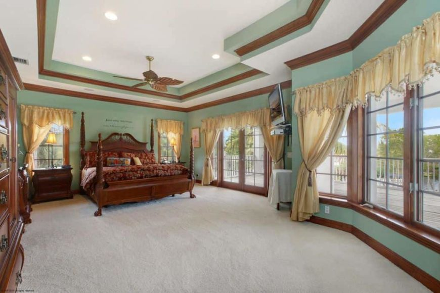Large master bedroom featuring a stunning tray ceiling and carpeted flooring. The large classy bed is surrounded by the room's green walls and large windows with gold-colored window curtains.