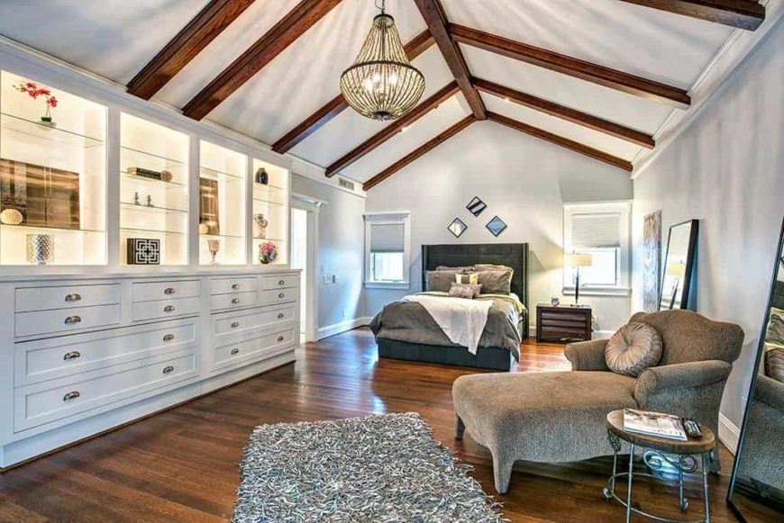 Master bedroom with white walls and hardwood flooring, along with a vaulted ceiling with exposed beams. The room offers large cabinetry and shelving with its own lighting.