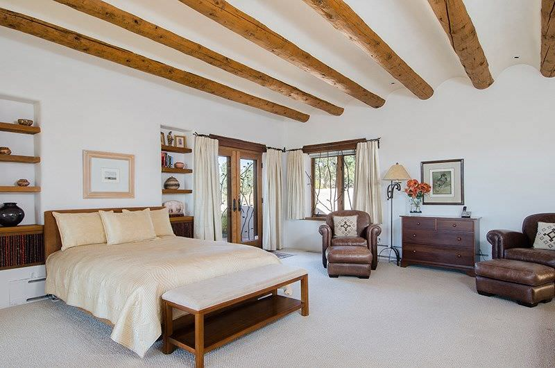 Large master bedroom with a nice bed along with built-in shelves on both sides. The room is surrounded by white walls and a white ceiling with exposed beams along with carpeted flooring.