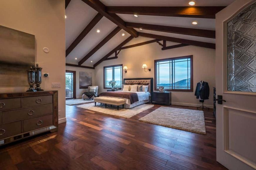 Large master bedroom with a vaulted ceiling with exposed beams together with hardwood flooring. The room offers a classy bed lighted by wall lights.