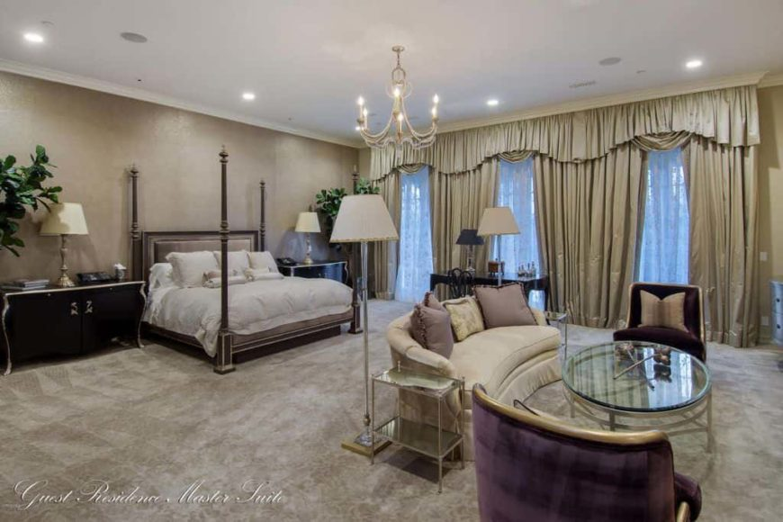 Large master bedroom featuring an elegant bed set along with a personal living space with a set of classy furniture. The room features a gorgeous chandelier, lovely window curtains and gray carpet flooring.