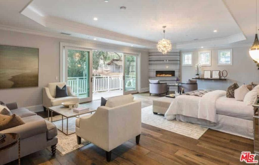 Large master bedroom featuring a white tray ceiling and hardwood flooring. The room offers a personal living space and a modish gas fireplace in the corner.