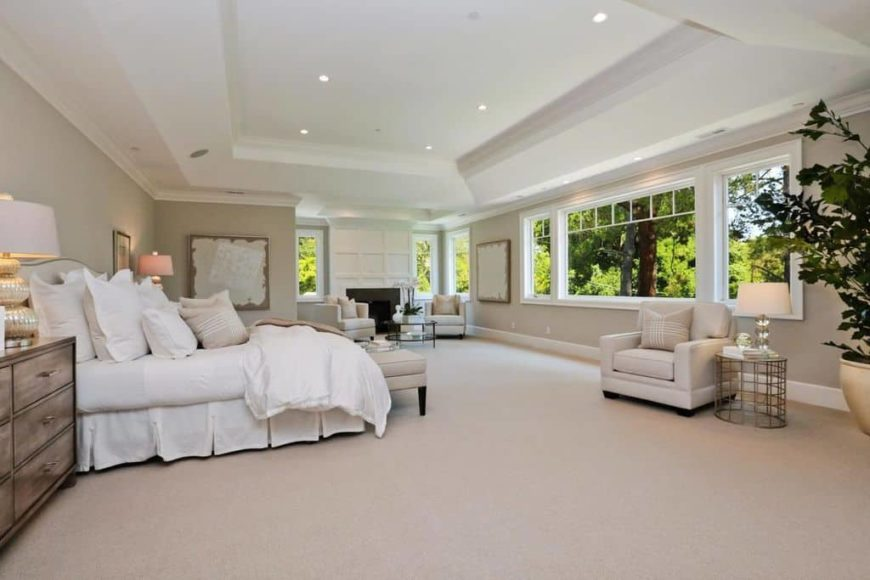 Spacious master bedroom with gray walls, carpeted floors and a white tray ceiling. The room has a large bed and a sitting area next to the room's fireplace.