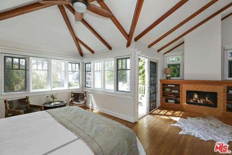 This master bedroom is surrounded by white walls and a white ceiling with exposed beams. The room also offers a fireplace with built-in shelving on both sides.