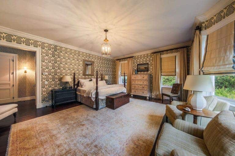 Large master bedroom featuring with elegant decorated walls along with hardwood floors topped by a large area rug. The room is lighted by a fabulous ceiling light.