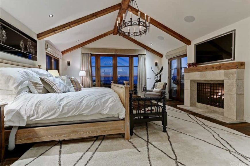 Large master bedroom featuring a white vaulted ceiling with exposed beams along with hardwood flooring topped by a large stylish area rug. The room offers a large comfy bed and a large fireplace with a TV above it.