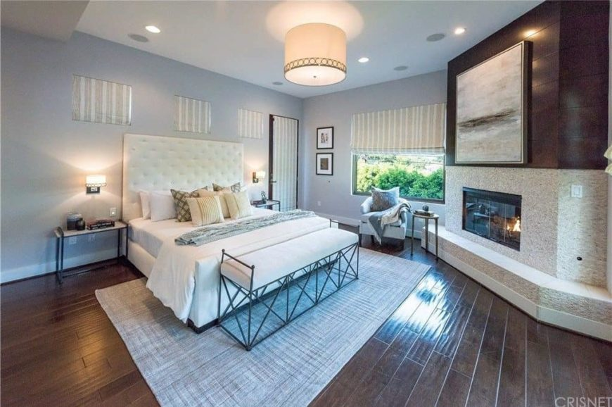 Large master bedroom with gray walls and hardwood flooring. The room has a classy bed set and a large corner fireplace.