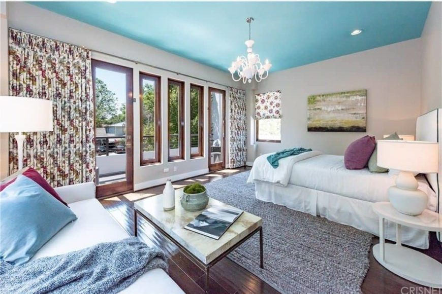 Master bedroom with a sky blue sky and hardwood flooring. The room offers a white bed matching the white large couch on the side.