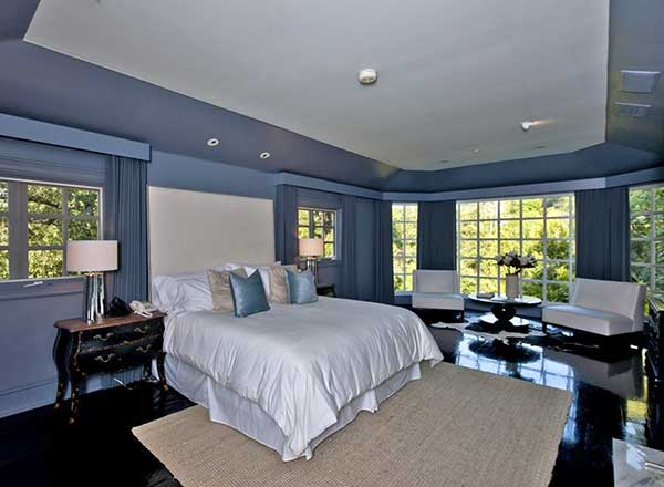 Large master bedroom featuring blueish gray walls and dark hardwood floors. The room offers a comfy bed lighted by classy table lamps. The room also offers a sitting space on the side.