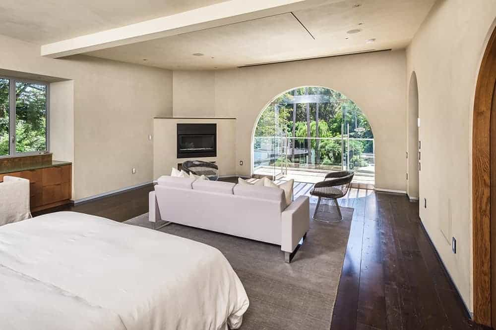 Mediterranean master bedroom featuring hardwood flooring. The room offers its own living space featuring a white couch and a fireplace in the corner.
