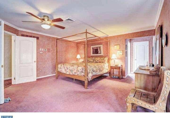 Spacious master bedroom featuring decorated pink walls and pink carpet flooring, together with the room's large classy bed lighted by two table lamps.