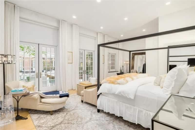 Large master bedroom featuring white walls and a white ceiling. There's a large bed along with comfy chairs.