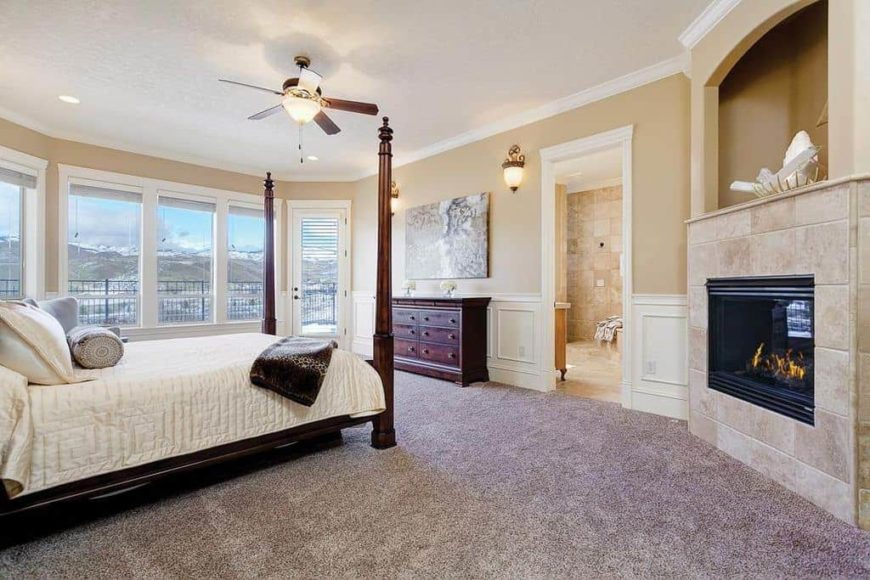This master bedroom offers a classy bed along with a corner fireplace. The room also offers its own large bathroom.