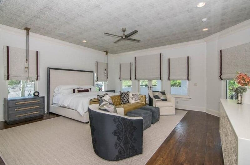 Large master bedroom with white walls and hardwood flooring. The room offers a nice cozy bed along with a small living space set on the area rug.