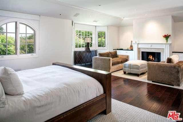 This master bedroom with white walls and hardwood flooring offers its own living space with a fireplace.
