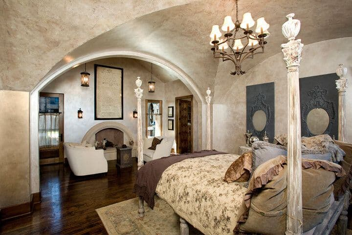 Master bedroom boasting a groin vault ceiling and hardwood flooring. The room boasts a classy bed set lighted by a gorgeous chandelier, along with a sitting area next to the fireplace.