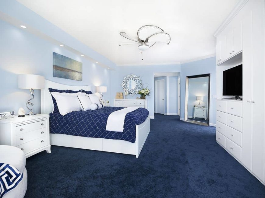 Large master bedroom featuring sky blue walls and navy blue carpet flooring. The room has a large white and blue bed set with white bedside tables topped by classy table lamps.