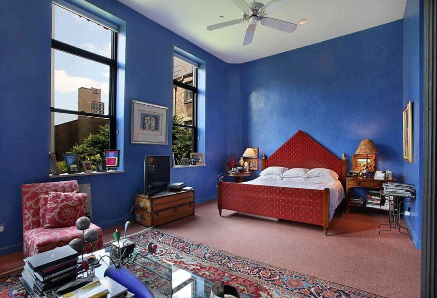 Large master bedroom featuring indigo blue walls and red carpet flooring. The room offers a nice red bed set.