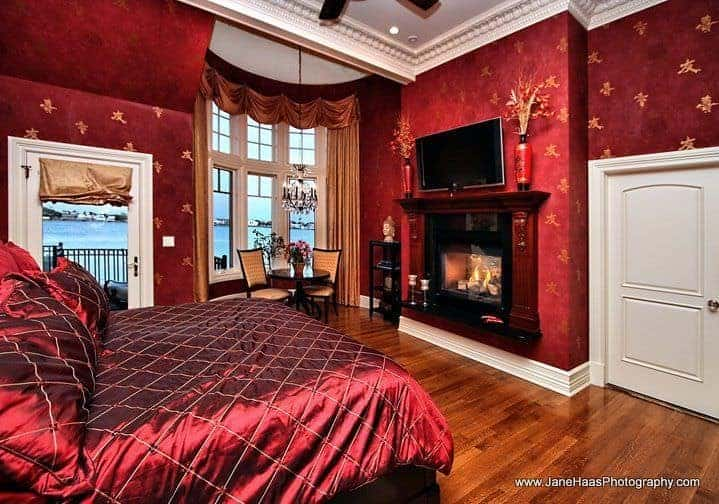 Master bedroom boasting elegant decorated red walls along with a red velvet bed set. The room also offers a gorgeous fireplace and a widescreen TV on the wall.