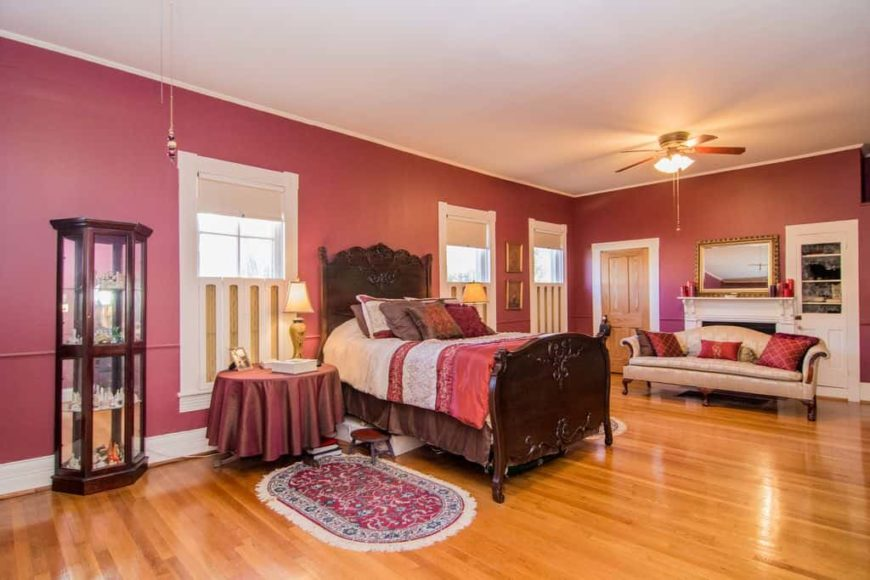 Large master bedroom featuring red walls and hardwood floors, together with the white regular ceiling. The room has a gorgeous bed setup and a nice couch on the side near the fireplace.