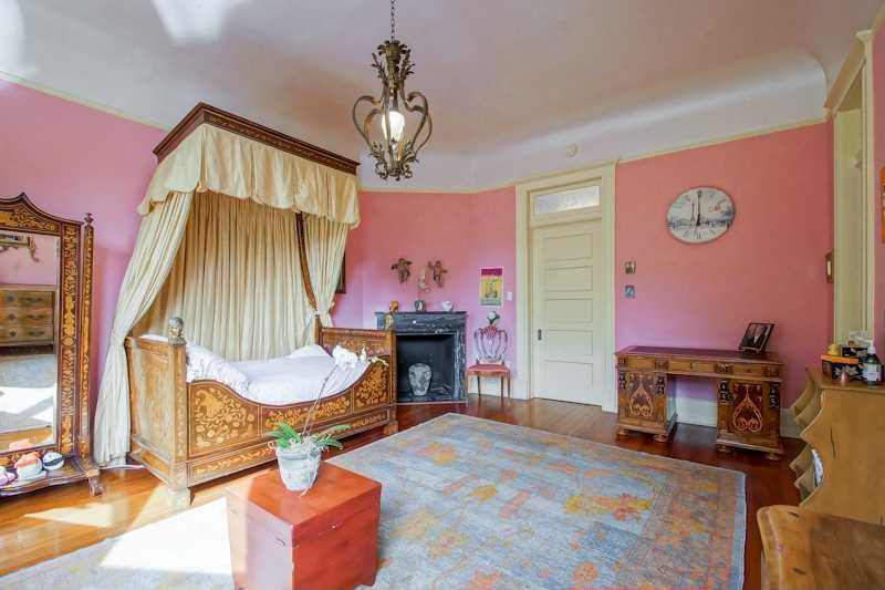 Large women's bedroom boasting a set of vintage-style furniture and bed set surrounded by pink walls.
