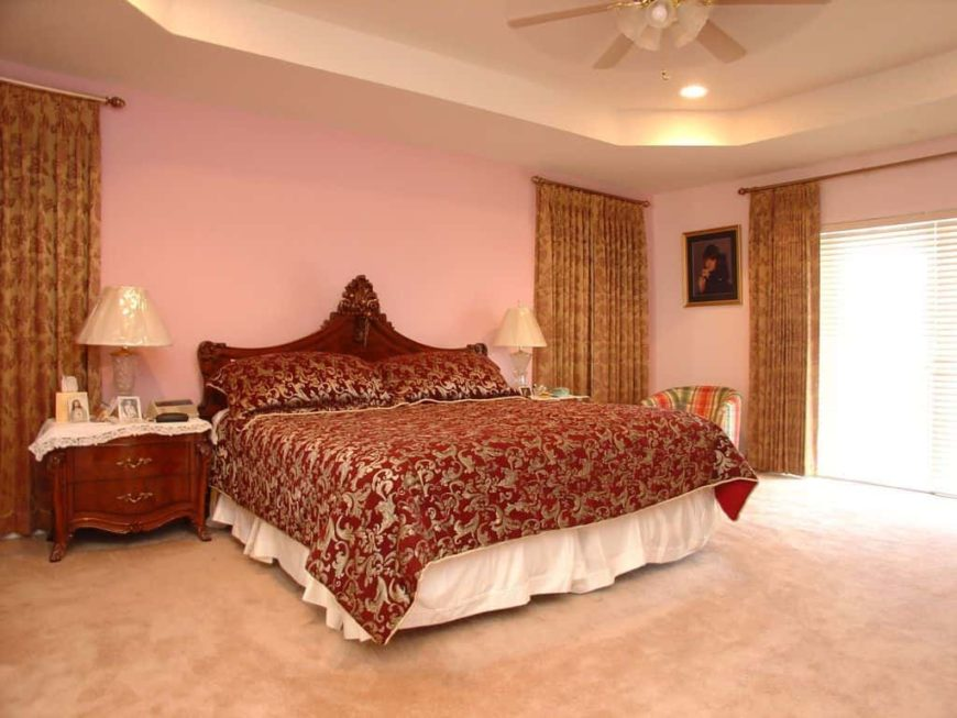 A women's master bedroom boasting an elegant bed set lighted by two classy table lamps. The window curtains add elegance to the room.