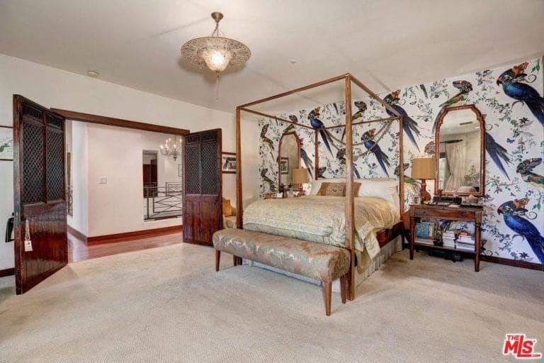 Spacious master bedroom with a beautiful decorated wall, a classy bed set and carpeted flooring.