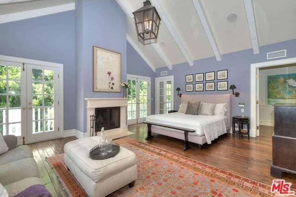 Large master bedroom featuring blue walls and hardwood flooring, along with a tall ceiling. The room has a large comfy bed, a personal living space with a couch and a fireplace.