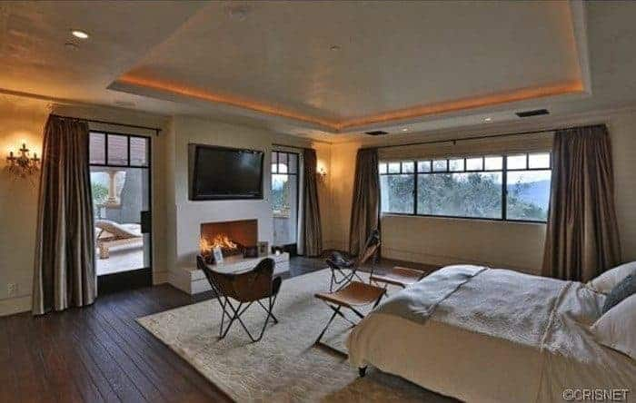 Large master bedroom featuring hardwood flooring and a tray ceiling. The room has a fireplace and a large widescreen TV in front of the bed.
