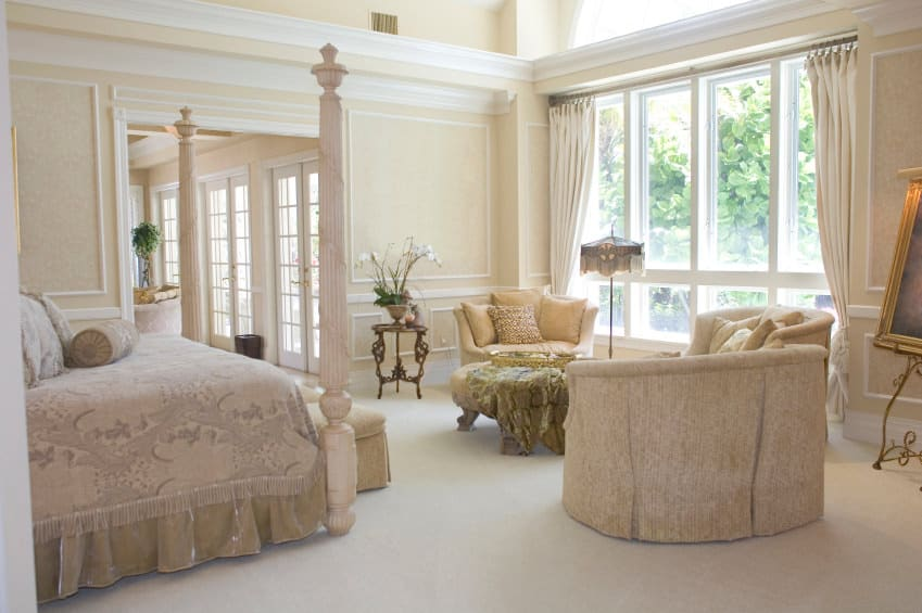 Classy master bedroom featuring lovely walls and an elegant bed set, along with a sitting space in front of the bed set.
