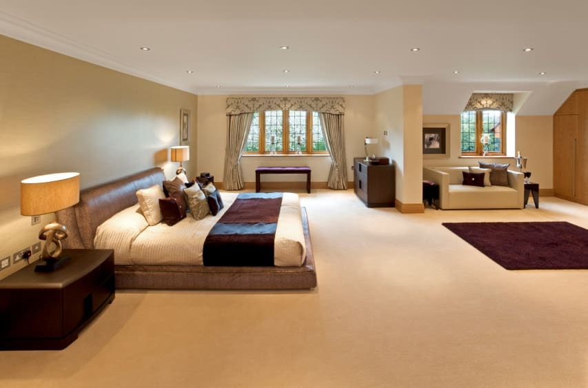 Huge master bedroom boasting beige walls and carpeted flooring. There's an extra-large bed lighted by two classy table lamps. There's a couch on the side of the room as well.