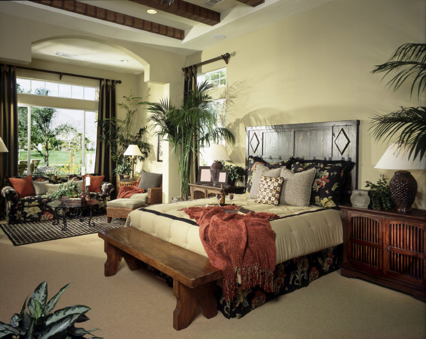 A focused shot at this master bedroom's stylish bed set. The room also has a small living space near the windows.