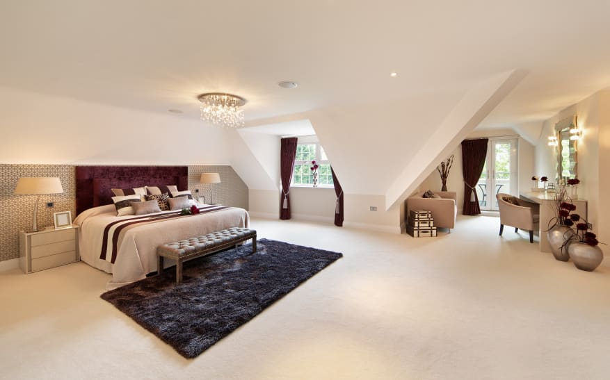 Huge master bedroom with white walls and ceiling, along with white carpet flooring. The room boasts a classy large bed set lighted by a gorgeous ceiling light together with two table lamps. The room also has a make-up desk on the side.