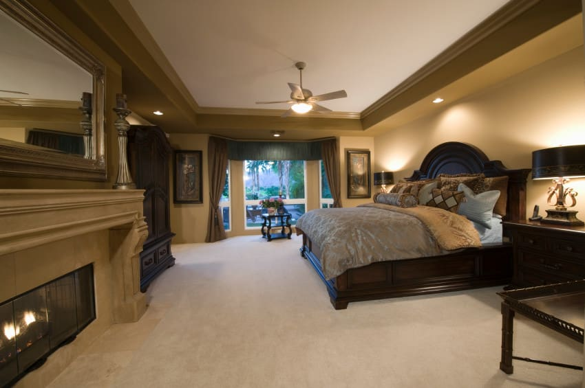 Huge master bedroom with elegant brown walls and a tray ceiling, together with carpeted flooring. The room offers a large bed and a large fireplace.
