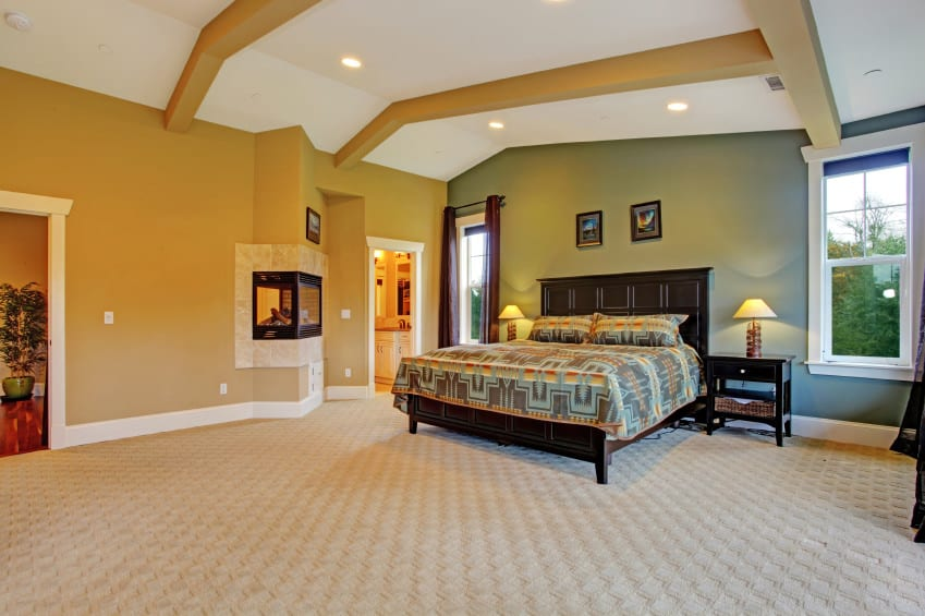 Spacious master bedroom with brown walls and classy carpet flooring, along with a ceiling with beams. The room offers a nice large bed and has its own bathroom too.