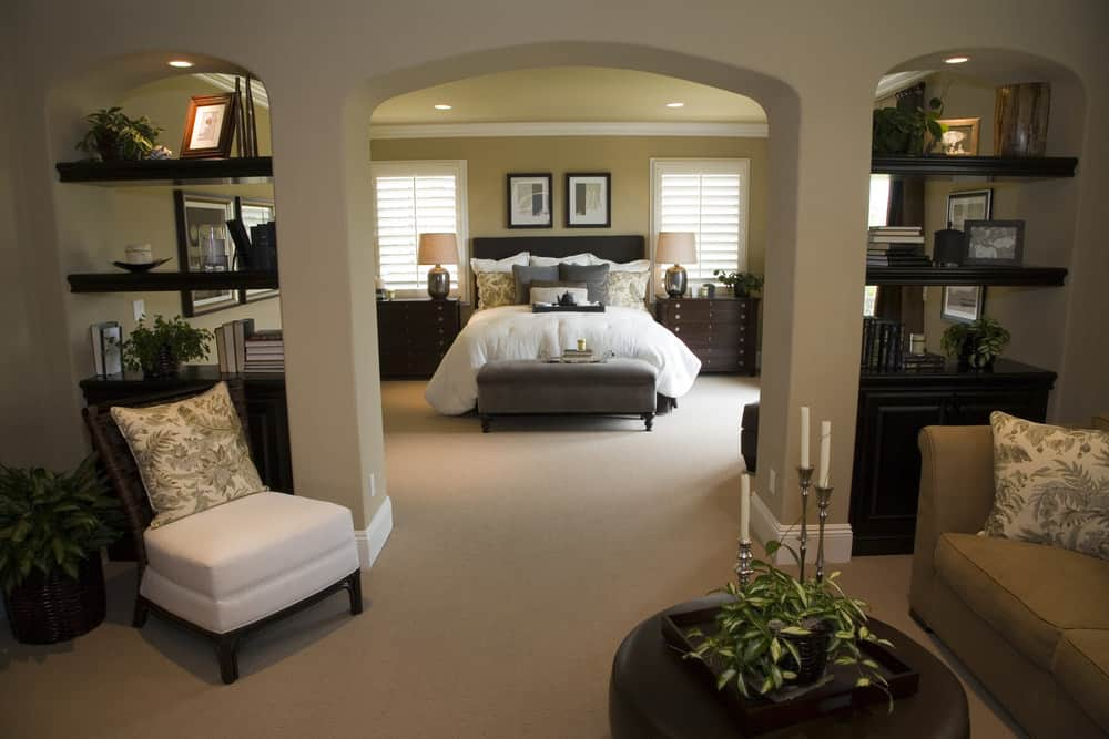 Large master bedroom with a cozy bed with two bedside tables along with built-in shelves and a small living space.