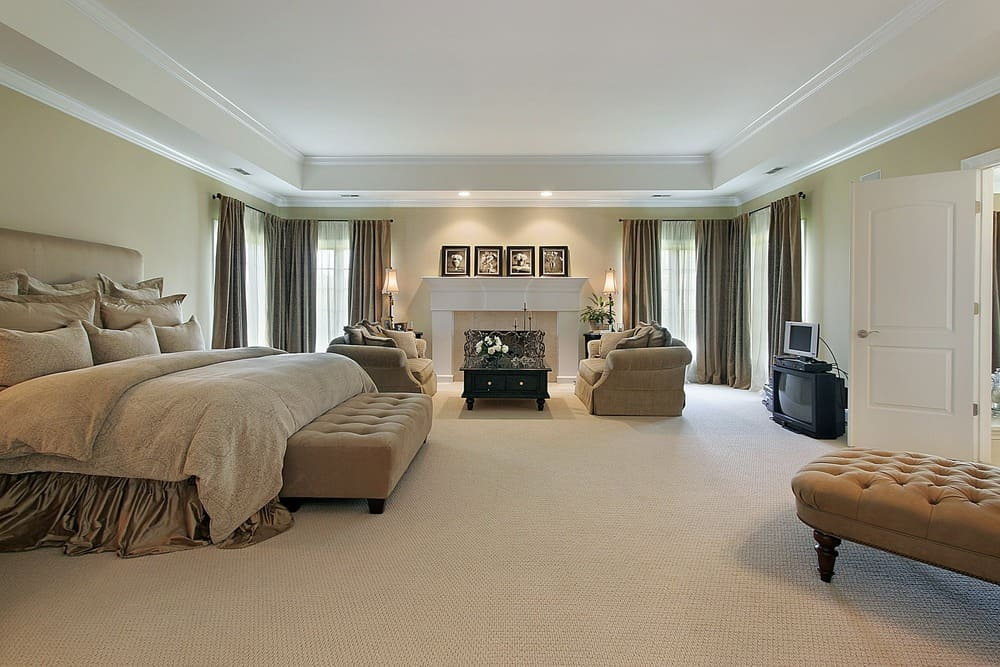 Spacious master bedroom boasting a large luxurious bed along with a personal living space with a large fireplace. The room has beige walls, carpeted flooring and a white tray ceiling.