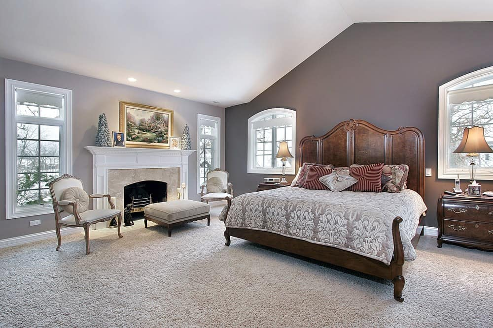 Large master bedroom with a classy large bed set ad a fireplace with seats nearby, surrounded by gray walls, carpeted flooring and a white ceiling.