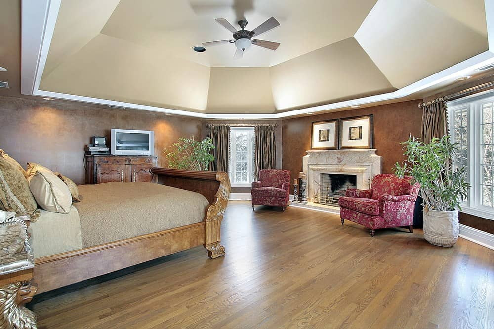 Large master bedroom boasting a stunning ceiling and elegant brown walls, along with hardwood flooring. The room boasts a large and classy bed along with elegant seats near the large fireplace.