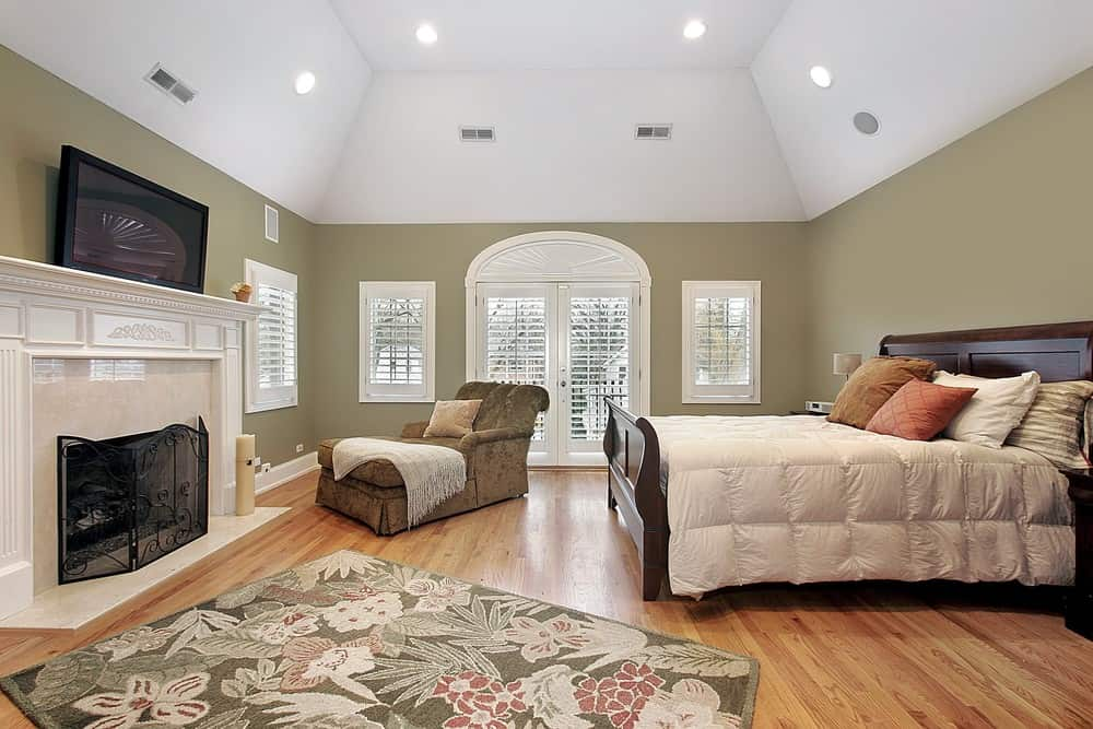 Large master bedroom boasting a tall white ceiling, gray walls and hardwood flooring. The room has a large bed and a fireplace in front.