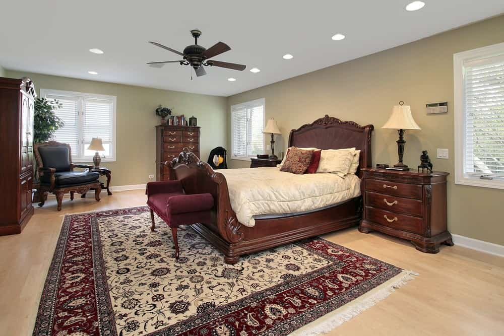 Large master bedroom with a regular white ceiling, gray walls and hardwood flooring topped by a large area rug. The room has matching pieces of furniture as well.