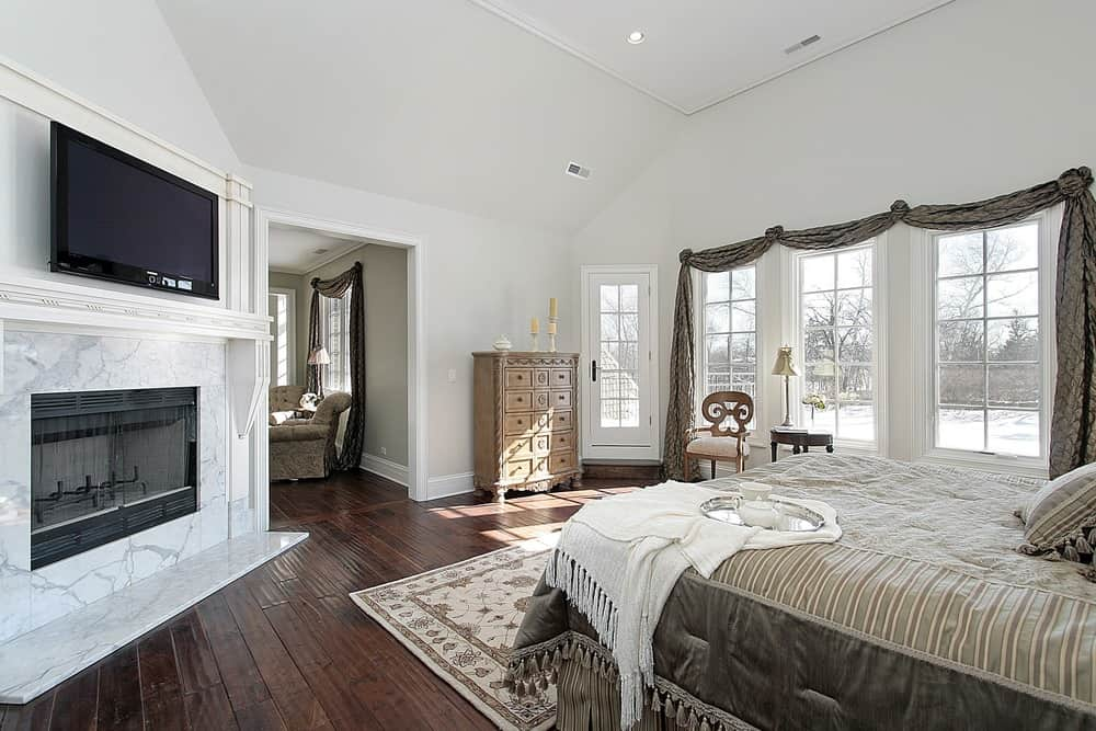 Master bedroom featuring white walls and a tall ceiling together with hardwood flooring. The room offers a fireplace and a widescreen TV just above it.