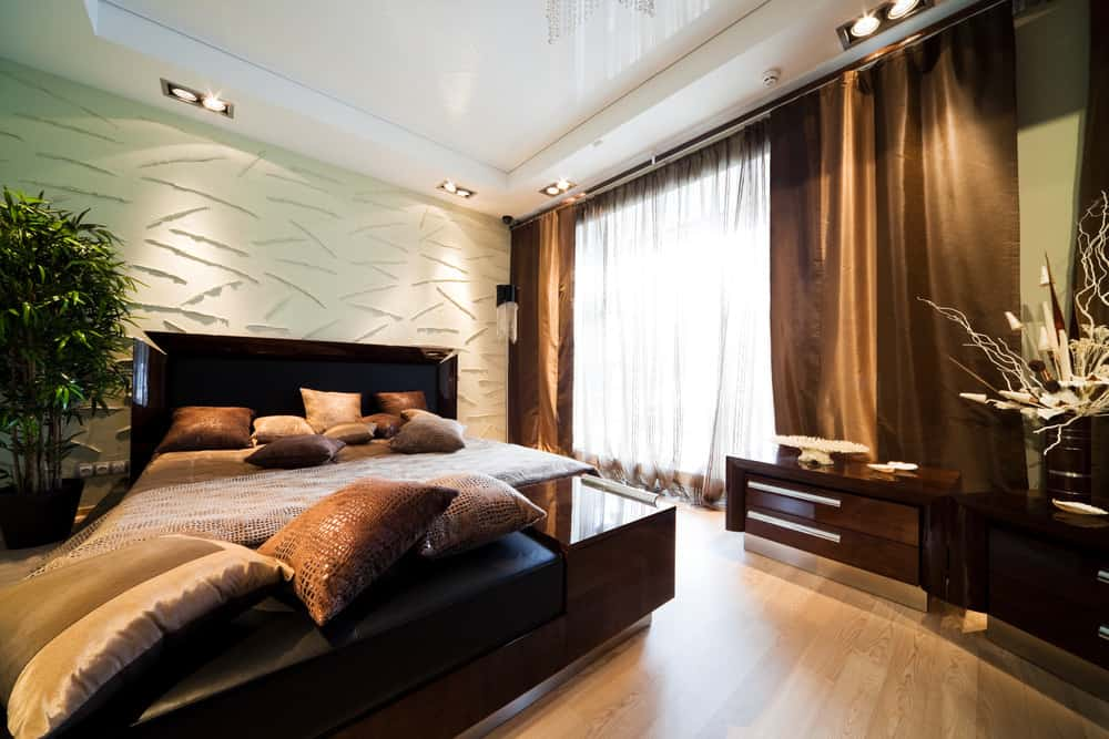 A luxurious master bedroom boasting an elegant bed set with elegant window curtains. The room offers a gorgeous tray ceiling and a decorated wall behind the bed set.